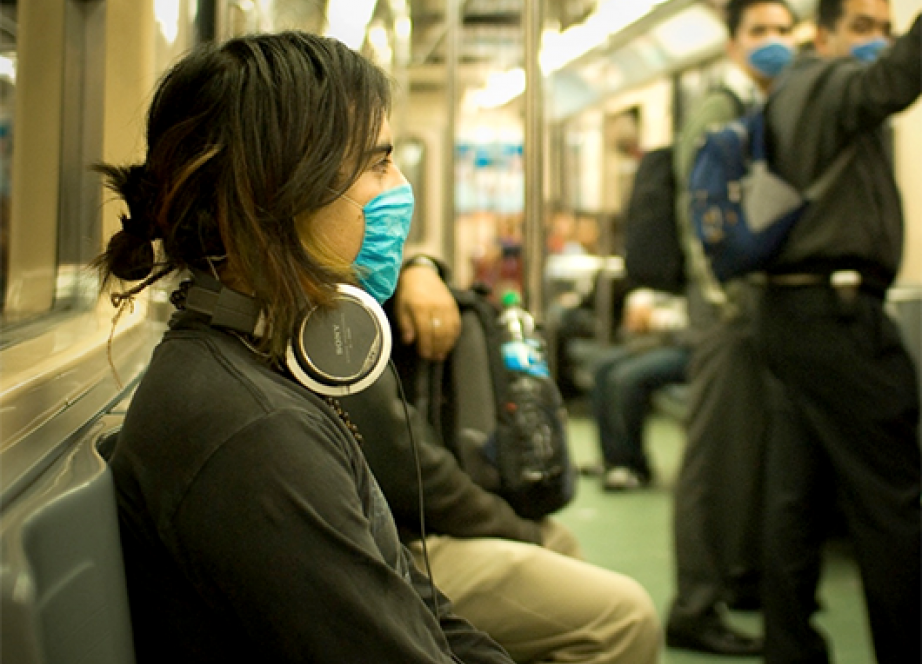Woman on a train wearing a filter mask