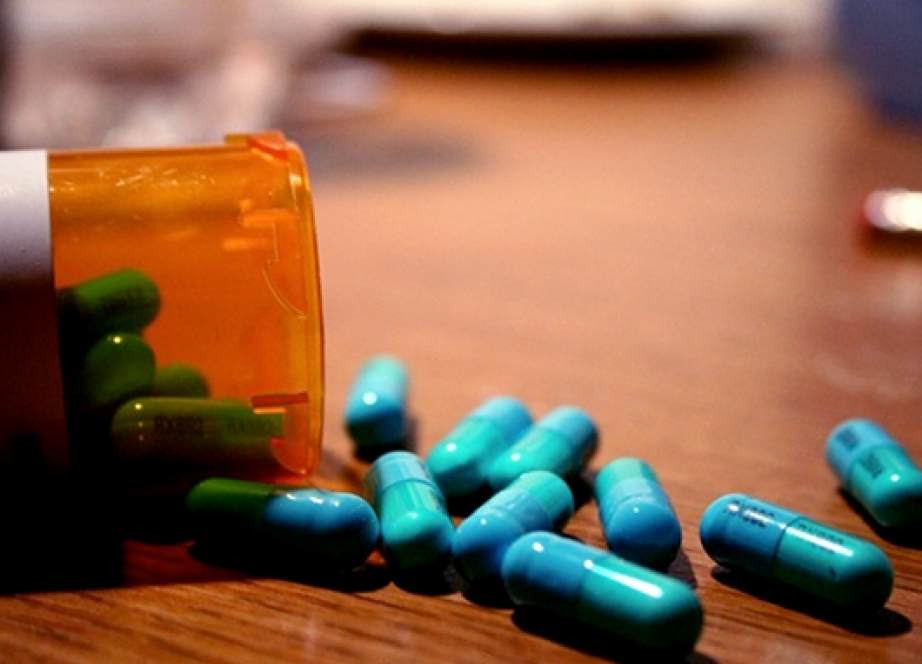 A medicine bottle with pills spilling out