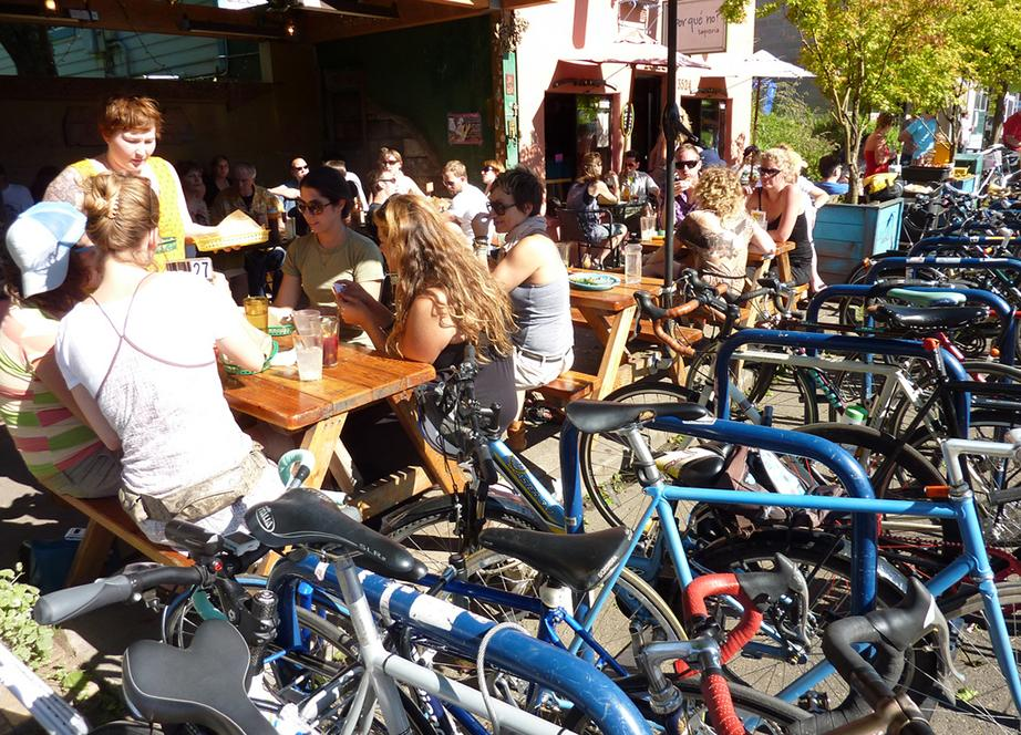 People eating at a restaurant with ample bicycle parking