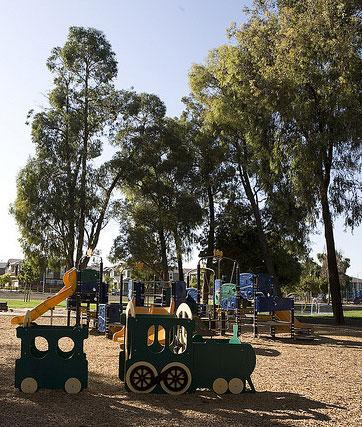 A children's playground with trees